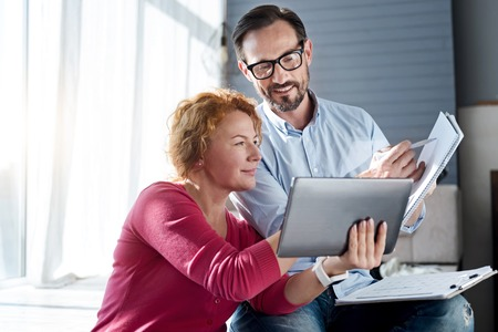 sharing information: Sharing information. Pretty ginger woman holding tablet while standing near her husband with glasses pointing at notebook.