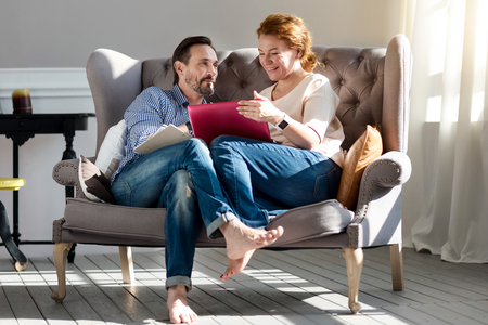 holding notes: Sweet home. Nice adult couple sitting on grey vintage couch barefoot, holding notes and using laptop.