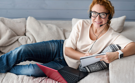 self employed: Self employed. Pretty smiling ginger woman wearing headphones with microphone making notes and using laptop while lying on couch.