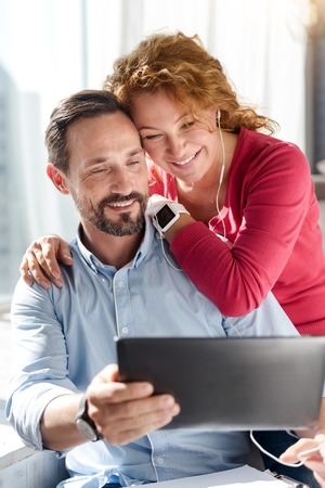 Using technologies. Handsome bearded man holding tablet and taking photos with his wife hugging him near window.