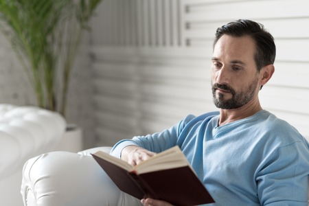 turning page: Involved in reading. Serious nice adult man holding a book and turning the page while reading a story Stock Photo