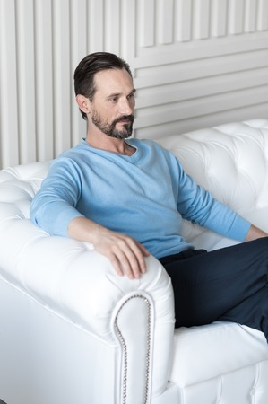 confidently: Feeling confidently. Good looking serious bearded man sitting on a white sofa and crossing his legs while thinking about something