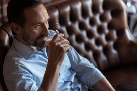 sip: My favourite beverage. Good looking optimistic man holding a glass and taking a sip of whisky while drinking alcohol