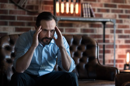 self employed: Involved in the thinking process. Handsome self employed stylish businessman sitting on the couch and putting his hands to the head while being involved in the thinking process