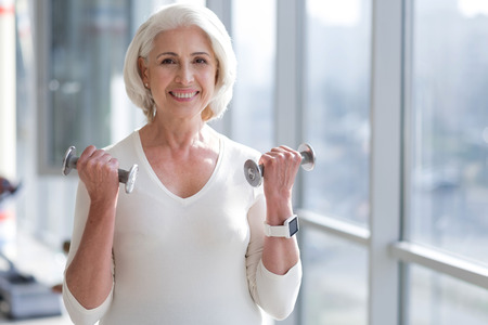 staying fit: Staying fit. Senior slim woman smiling and lifting weights while exercising in the gym. Stock Photo