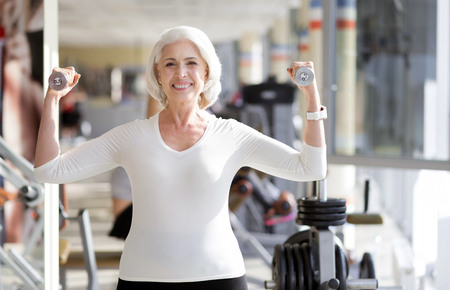 keeping fit: Fitness as lifestyle. Joyful sporty senior woman keeping fit and smiling while using weights during gym exercise.