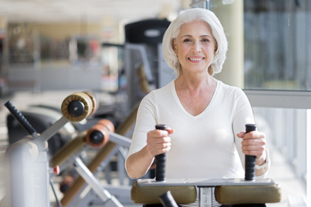 staying fit: Cheerful workout. Attractive senior joyful woman smiling and staying fit by using equipment in a gym. Stock Photo