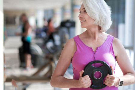 Happy fitness. Beautiful active woman turning head and smiling while exercising with plate in a gym. Stock Photo
