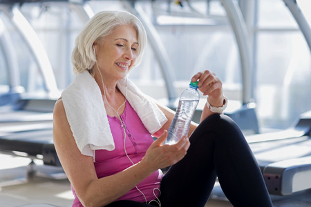 Great training. Emotional pretty senior woman smiling and holding a bottle of water while resting on the floor in a gym.