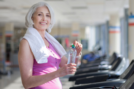 Progressive training. Beautiful happy senior woman smiling and drinking water while having a rest after sport. Stok Fotoğraf