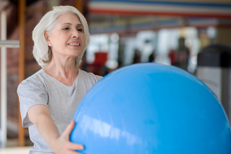 One more time. Glad senior charming woman smiling and holding fit ball while exercising in a gym