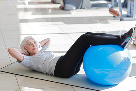 I will do it. Ambitious pretty senior woman laying on a floor and putting legs on a fit ball while doing sit ups. Stock Photo