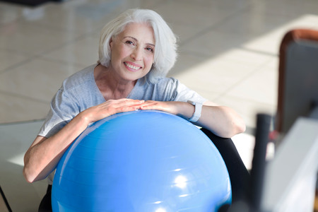 overjoyed: Time to relax. Overjoyed pretty senior woman sitting on a floor and putting hands on fit ball while resting after physical training
