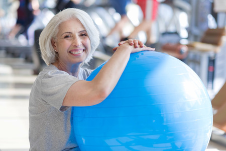 keeping fit: Finishing training. Pleasant beautiful senior woman smiling and keeping fit ball while sitting on a floor in a gym.