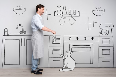 not forget: Do not forget about your pets. Good looking delighted positive man standing in a kitchen and holding the fish while feeding the cat