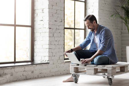 Written messages. Nice pleasant attractive man holding a laptop and looking at its screen while typing a message