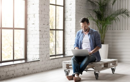 somebody: Interactive communication. Nice attractive joyful man holding a laptop and having an online chat with somebody while sitting in the room Stock Photo