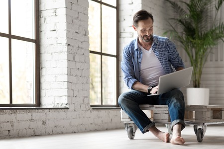 handome: Modern device. Happy joyful handsome man holding a laptop on his knees and typing a message while sitting on the Internet