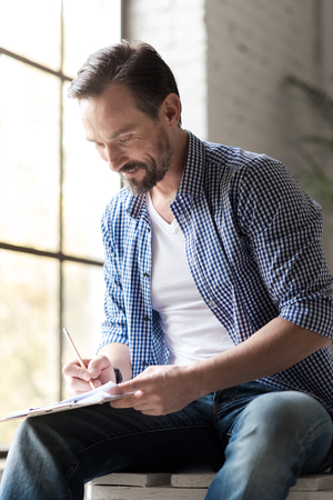 leaning forward: New ideas. Creative delighted handsome man leaning forward and looking at his notes while writing something there