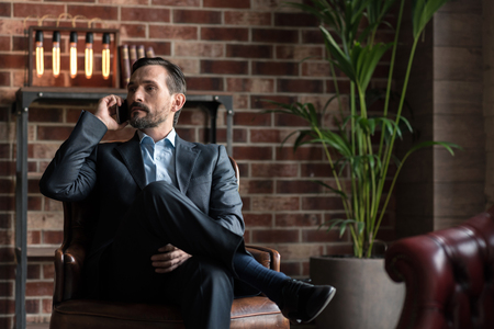 manhood: Involved in the discussion. Good looking attractive confident man sitting in an armchair and listening attentively to his interlocutor while having a conversation