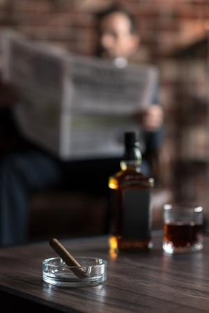 manhood: Preparing to smoke. Selective focus of a transparent glass ashtray with a cigar in it standing on the table near the bottle of whisky