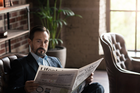 informed: Being informed. Pleasant good looking attractive man holding a newspaper and reading the latest news while being in the office
