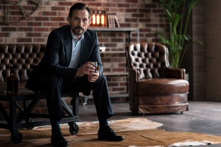 manhood: Strong and powerful. Handsome serious brutal businessman sitting on a small table and holding a glass of whisky while looking at you Stock Photo