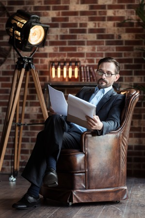 businesslike: Checking everything. Serious bearded confident man sitting in the armchair and crossing his legs while looking through his notes