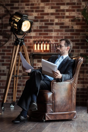 businesslike: Feeling comfortable. Nice pleasant handsome man wearing glasses and crossing his legs while sitting in the armchair