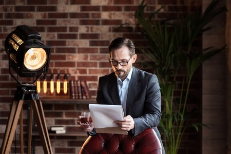 Working issues. Hard working self employed handsome businessman standing near the chair and holding a glass of whisky while reviewing some documents Stock Photo