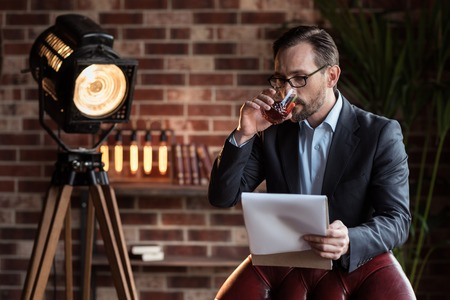 sip: Expensive alcohol. Handsome serious stylish man standing near the armchair and taking a sip of whisky while reading his notes