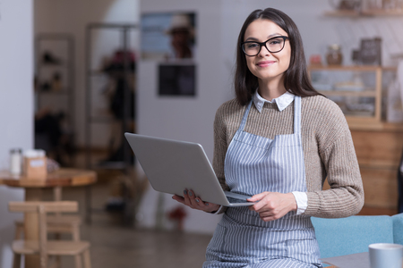 ambitious: Ready to work. Beautiful ambitious woman smiling and holding laptop while standing in a cafe.