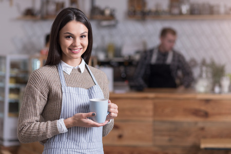 Tea time. Happy pretty woman smiling and holding cup of tea while standing in a cafe.