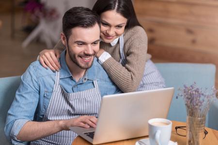 Negocio familiar. Mujer bonita y un hombre hermoso positivo sonriendo y usando la computadora portátil mientras está sentado en un sillón.