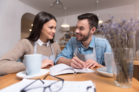 glad: Tasty working time. Glad happy couple of cafe owners smiling and making notes while sitting drinking coffee. Stock Photo