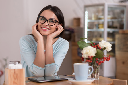 delightful relaxation. Happy emotional beautiful woman smiling and using her gadget while having a coffee in a cafe