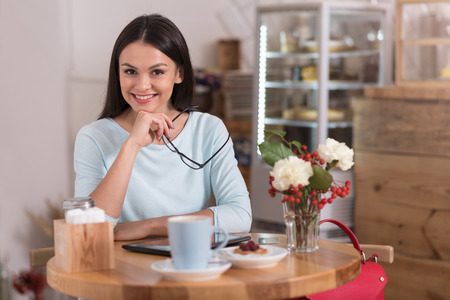 Delightful coffee break. Attractive satisfied delighted woman smiling and relaxing while visiting a coffee shop. Stock Photo
