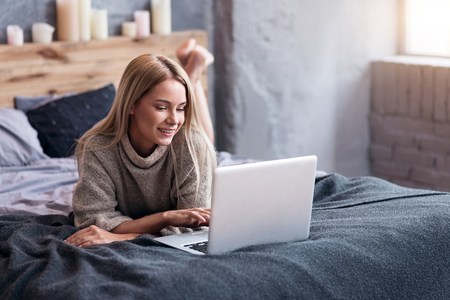 take it easy: Take it easy. Beautiful delighted young woman lying in bed and using laptop while relaxing.