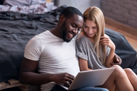 race relations: Weekend is fun. Joyful young international couple sitting in bedroom and using laptop while spending time together.