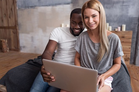 race relations: So interesting. Delighted young international couple watching film on a laptop together while relaxing in bed and spending time together.