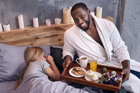 race relations: I care for you. Joyful African young man posing with a tray and giving breakfast to his wife in bedroom while she is sleeping. Stock Photo