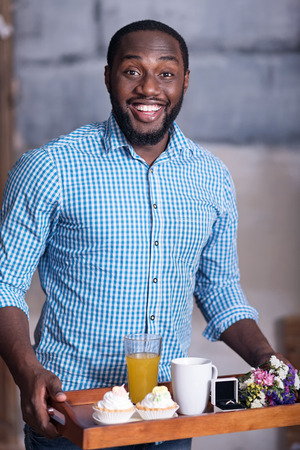 overjoyed: It is coming. African young overjoyed man preparing for marriage proposal while holding a tray with breakfast and the ring and smiling.