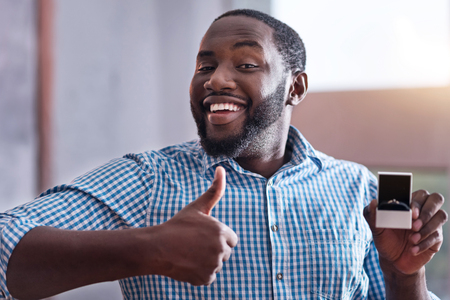 overjoyed: I am overjoyed. Happy young African man holding an engagement ring preparing for proposal and making approval gesture. Stock Photo