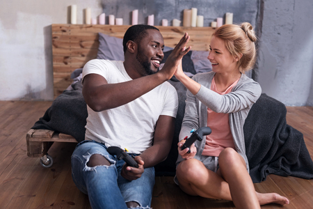 overjoyed: Our happy times. Overjoyed international young couple enjoying video games while sitting in bedroom and smiling. Stock Photo