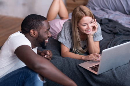 race relations: Home coziness. Young international delighted couple using laptop while lying in bedroom and smiling. Stock Photo