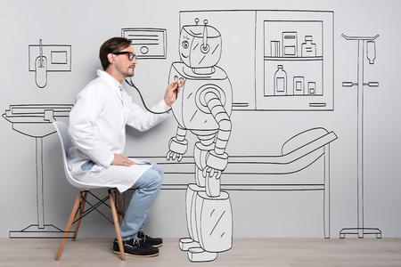 talented: Everyone have a heart. Young talented man using stethoscope and examining robots heart while sitting on the chair Stock Photo