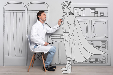 delighted: Everyone is a hero. Delighted handsome man smiling and examining Super hero while sitting chair.