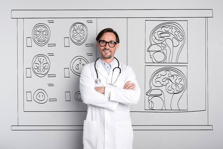 bespectacled man: Interested in brain. Inspired handsome man smiling and folding his hands while standing against the painted wall. Stock Photo