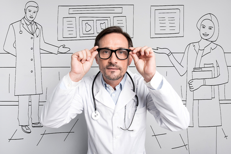 bespectacled man: Clear eyes. Serious pleasant man looking right and touching his glasses while standing at hospital.
