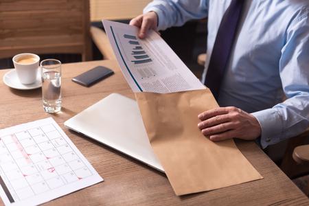 diligente: Preparados para ser enviados. Diligente trabajador hombre responsable en posesión de documentos y ponerlos en el sobre mientras está sentado en la mesa